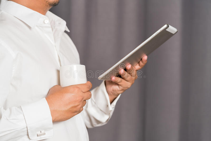 Man having glass of water and holding digital tablet in office stock photography