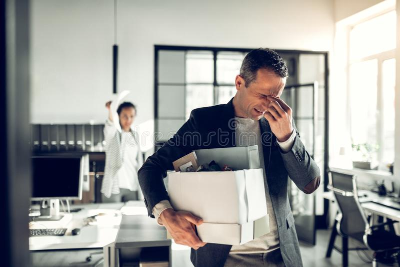 Man having headache while listening to his crazy female boss royalty free stock photos