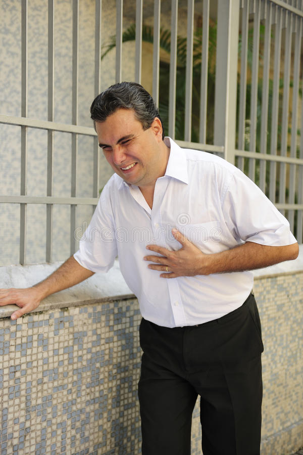 Man having a heart attack bending stock images