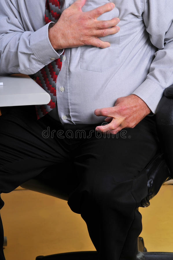 Man having heart attack at his desk stock images