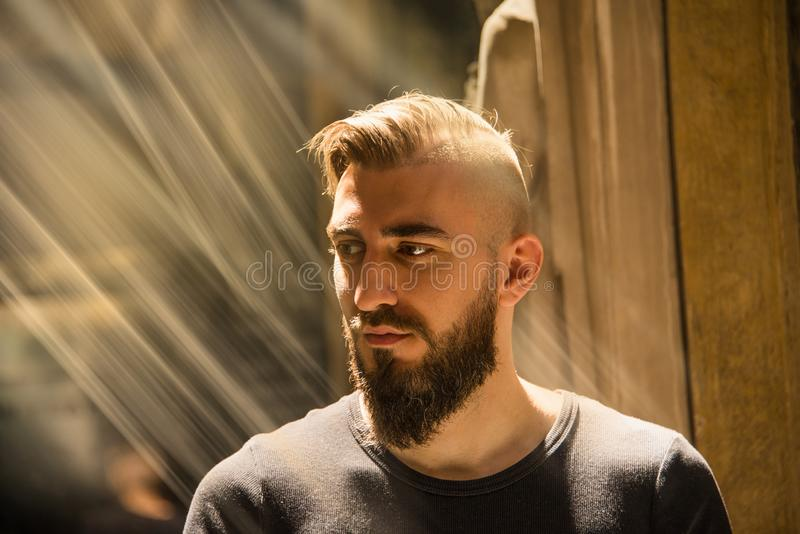A man is having an illumination moment with god. A man is having an illumination moment looking towards a harsh divine light that represents god or Jesus. He is royalty free stock photos