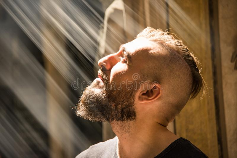 A man is having an illumination moment with god. A man is having an illumination moment looking towards a harsh divine light that represents god or Jesus. He is royalty free stock image