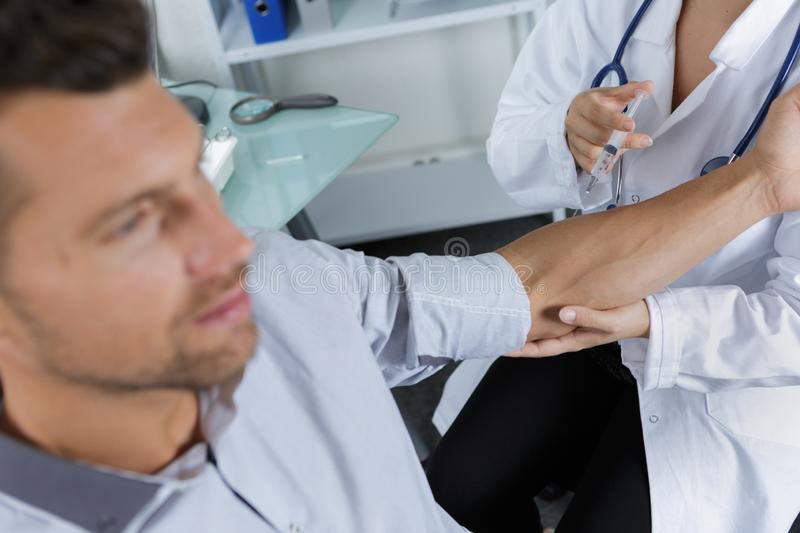 Man having injection in arm. Man stock images