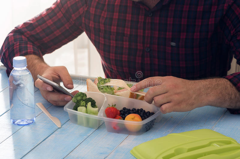 Man is having lunch healthy food sitting at wooden table stock images