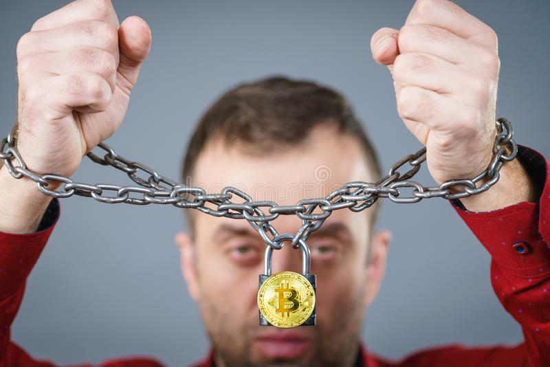 Man being tied up in block chain. Man having problems with crypto currency. Adult guy being tied up with block chain bitcoin stock photography