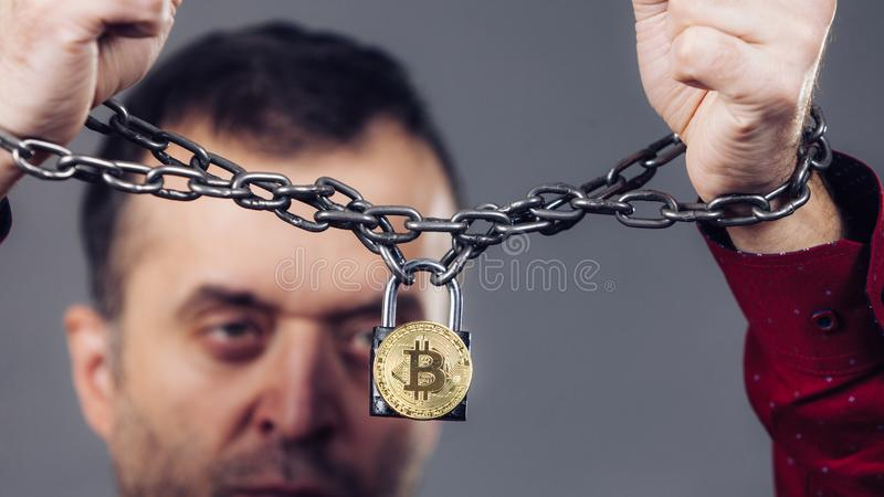 Man being tied up in block chain. Man having problems with crypto currency. Adult guy being tied up with block chain bitcoin royalty free stock images