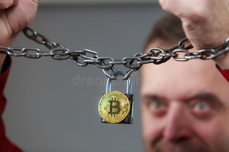 Man being tied up in block chain. Man having problems with crypto currency. Adult guy being tied up with block chain bitcoin royalty free stock photography