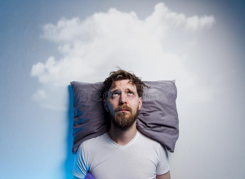 Man having problems/ insomnia, laying in bed on pillow. Looking up to gray cloud over his head, copy space royalty free stock image