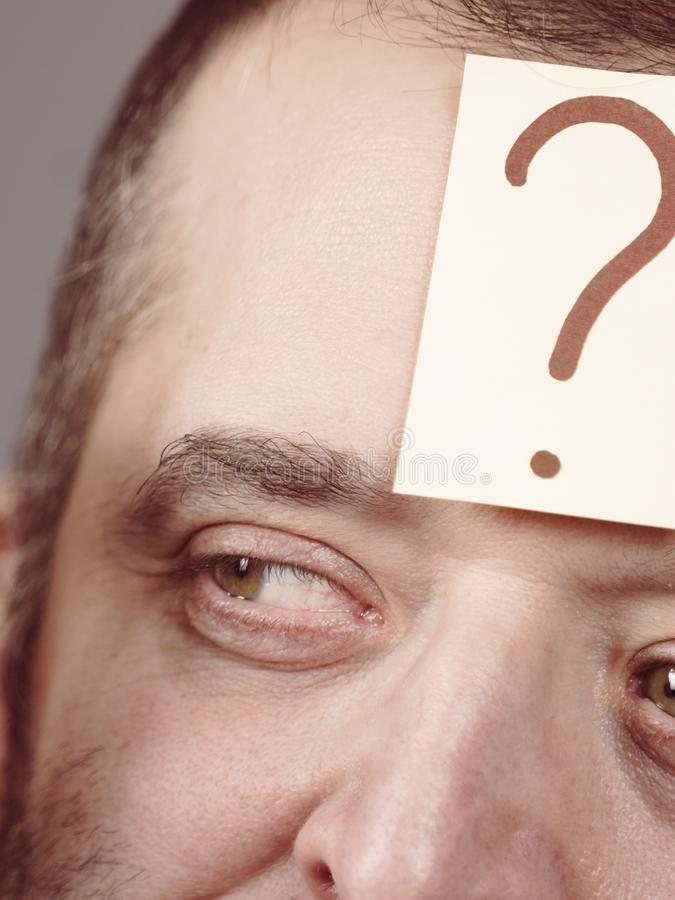 Man having question mark on his forehead stock images