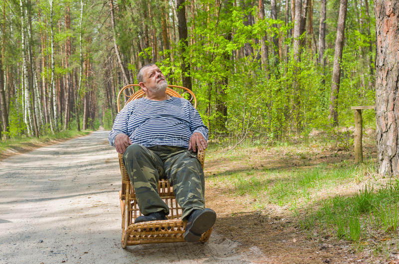 Man is having rest in forest sitting on a wicker rocking-chair stock photo