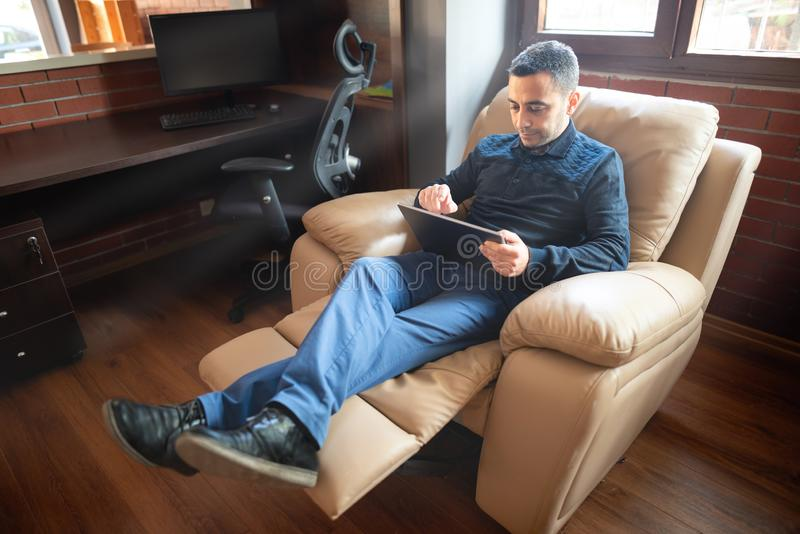 Man Having Rest In Office and Using Hisl Tablet stock images