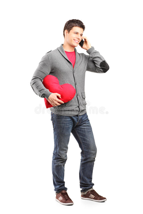 Man having a romantic conversation on the phone. Full length portrait of a man having a romantic conversation on the phone isolated on white background stock photo