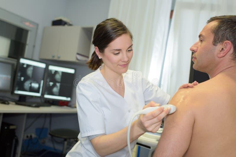 Man having shoulder ultrasound stock images