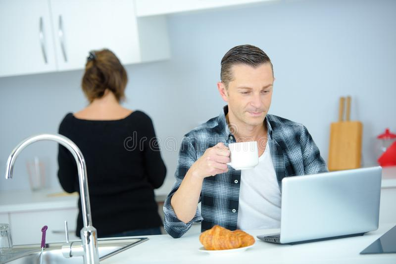 Man having snack while working with laptop in kitchen. Man royalty free stock photography