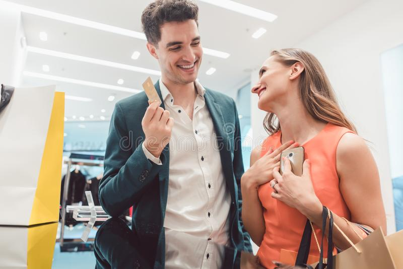 Man having to pay with credit card for fashion items his wife shopped. Happy Man having to pay with credit card for fashion items his wife shopped royalty free stock photos