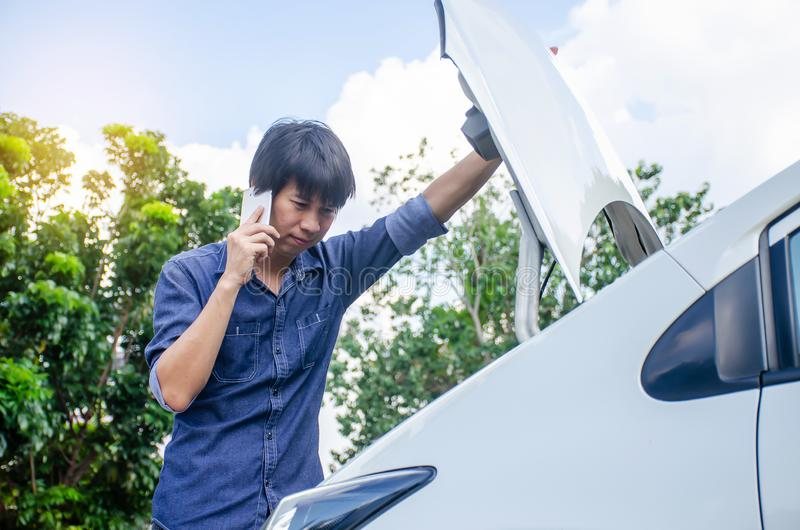 Man having trouble with his broken car and checking on a car engine and talking phone with someone about car for help stock image