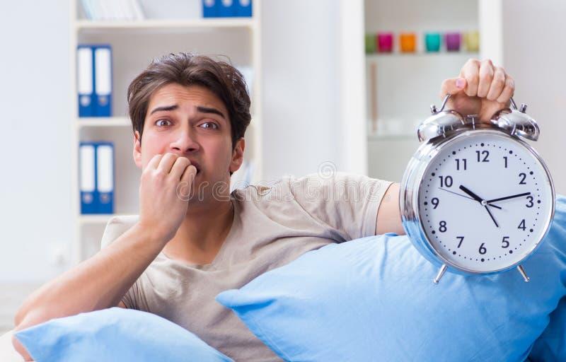 Man having trouble waking up with alarm clock stock image