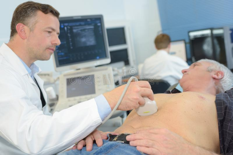 Man having ultrasound in abdomen. Man having an ultrasound in the abdomen stock image
