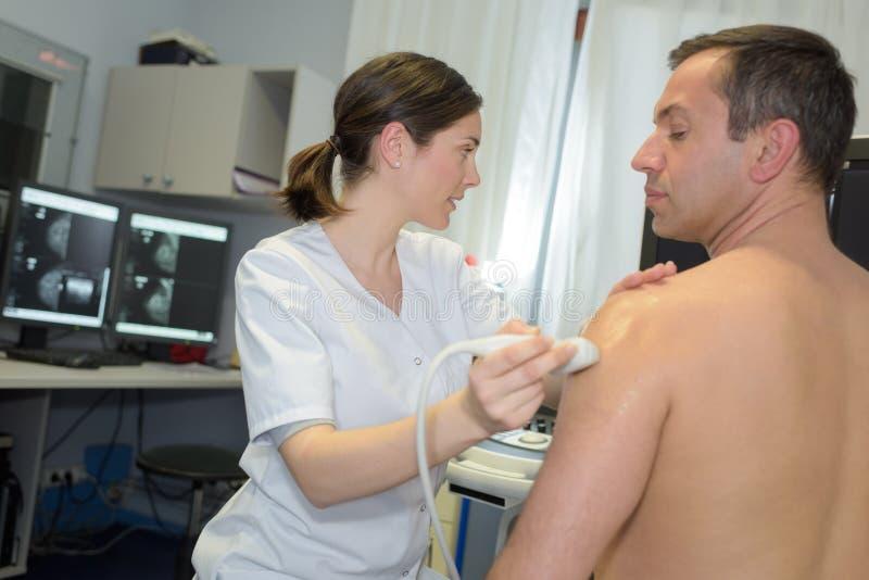Man having ultrasound on shoulder. Man having ultrasound on the shoulder stock photos
