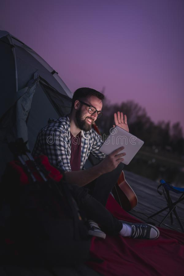 Man having a video call while camping on the lake stock photo