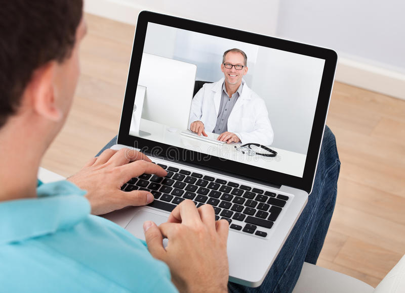 Man having video chat with doctor. On laptop at home stock photography