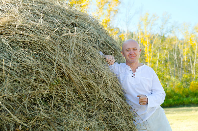 Man by haystack. A caucasian man in a white shirt rests against a haystack royalty free stock image