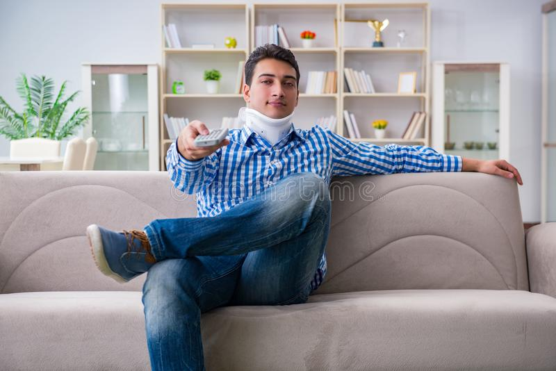 Man with a head neck spine trauma wearing a neck brace cervical. Collar watching tv at home stock image