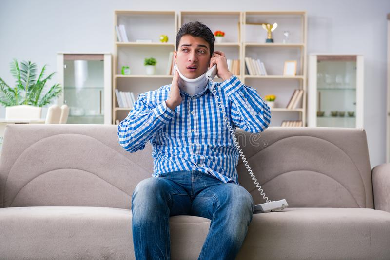Man with a head neck spine trauma wearing a neck brace cervical. Collar talking on phone royalty free stock image