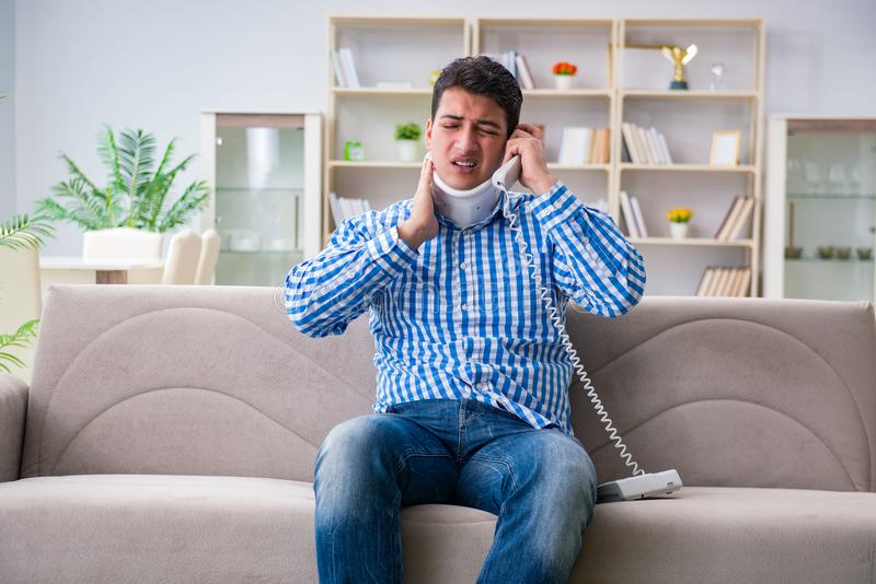 Man with a head neck spine trauma wearing a neck brace cervical. Collar talking on phone stock photos