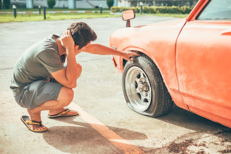 A man headache when car breakdown and wheel flat tire in parking royalty free stock photos