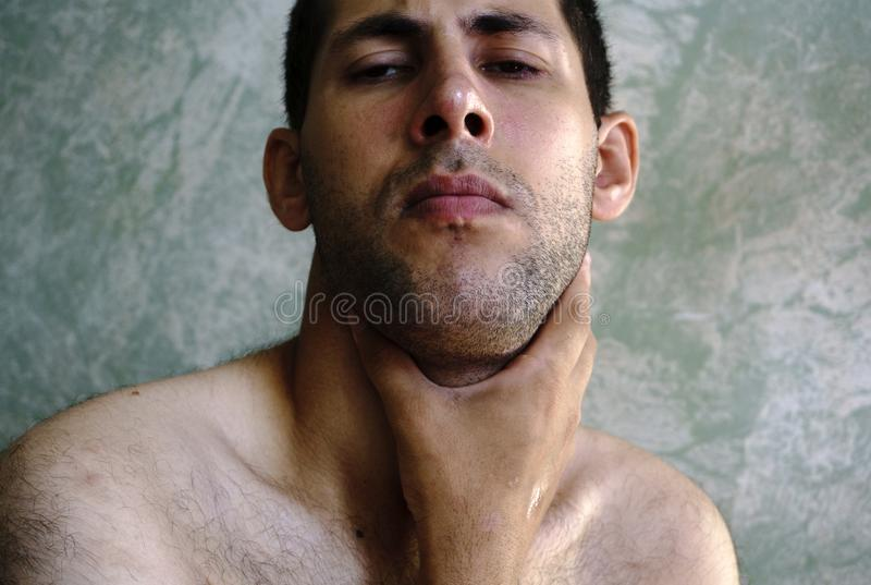 Man with headache and strong sore throat probably has cold.  stock images