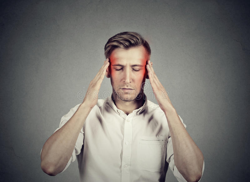 Man with headache thinking very intensely concentrating. Isolated on gray wall background royalty free stock image