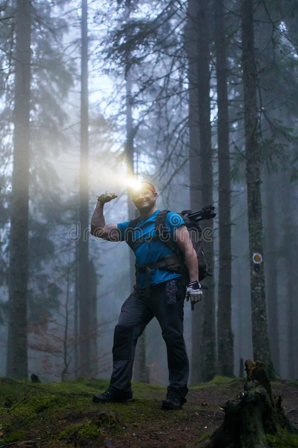Man with headlamp and backpack in the forest. Hiker with headlamp and backpack on a trail in the forest at night royalty free stock photos