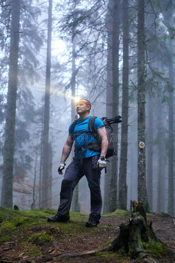 Man with headlamp and backpack in the forest. Hiker with headlamp and backpack on a trail in the forest at night stock image