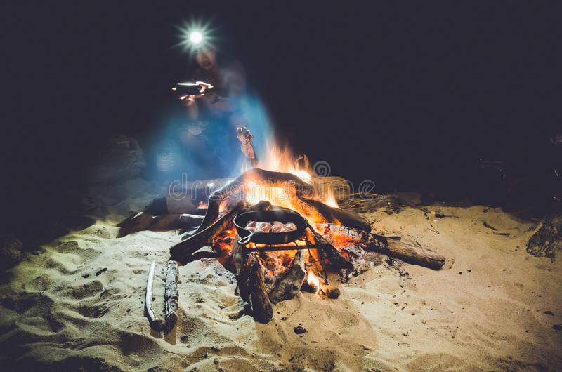 Man with headlamp next to campfire stock photography