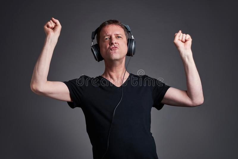 Man with a headphone. A middle age listening some music on the headphone and dancingr stock photos