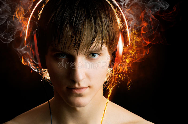 Man with headphones on. Man in headphones on the black background royalty free stock image