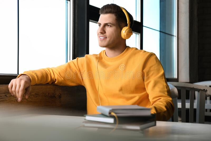 Man with headphones connected to book at table in cafe stock photography