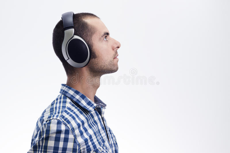 Man with headphones. Handsome young man with headphones, looks forward, isolated on white background stock image