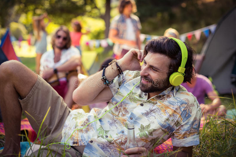 Man in headphones holding beer bottle at campsite. On a sunny day stock images