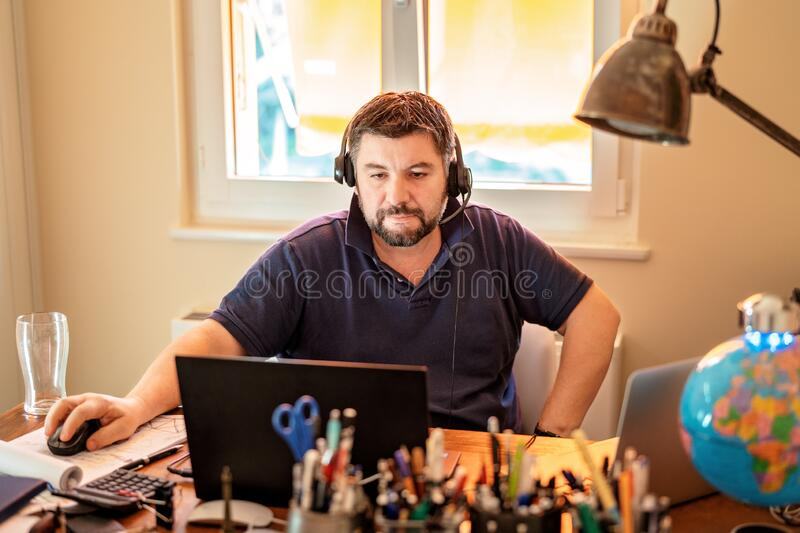 Man with headphones and microphone having conference call online sitting at home office with two laptops. Working from home during quarantine and self royalty free stock photo