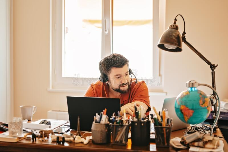 Man with headphones and microphone having conference call online sitting at home office with two laptops. Working from home. During quarantine and self royalty free stock photos