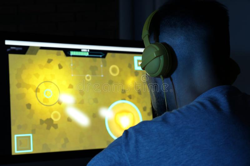 Man with headphones playing video game on computer in dark room stock photos