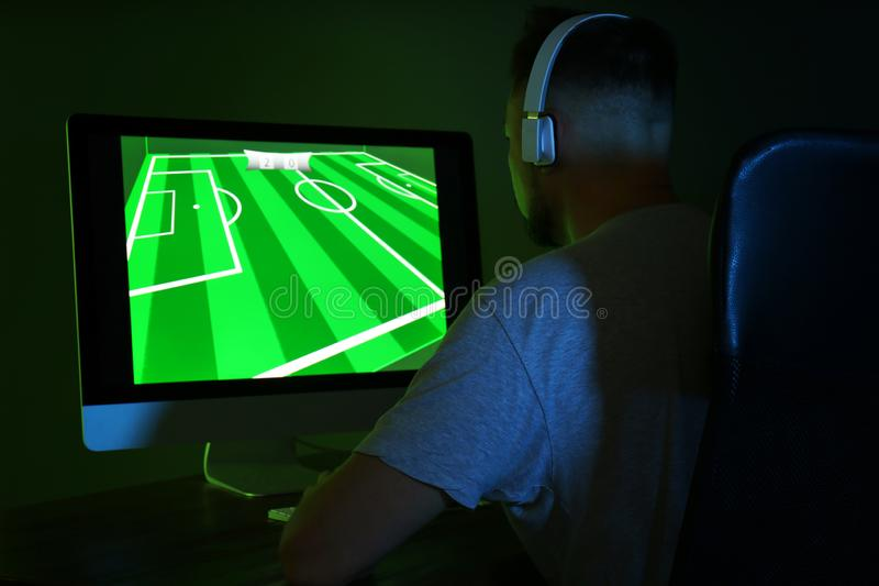 Man with headphones playing video game on computer in dark room royalty free stock image