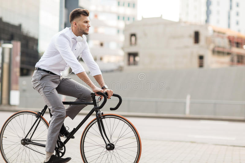 Man with headphones riding bicycle on city street royalty free stock image