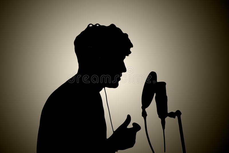 man in headphones singing into a microphone on a white backgroun stock photography