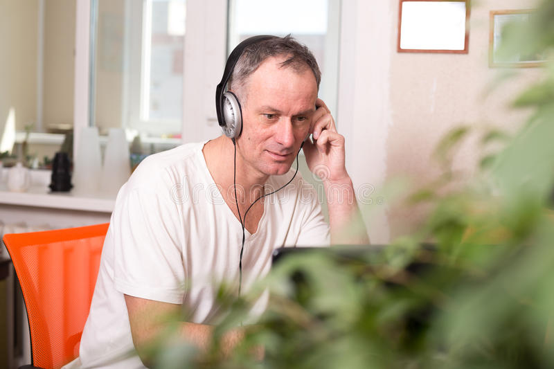 Man in headphones sits near the computer, experiencing stress. And tensely looks at the screen on the light blurred background - office at home, freelance job royalty free stock photo