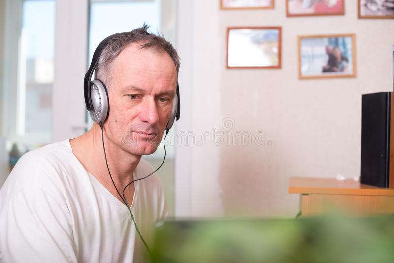 Man in headphones sits near the computer - office at home. Engaged man in headphones sits near the computer and tensely looks at the screen on the light blurred stock image
