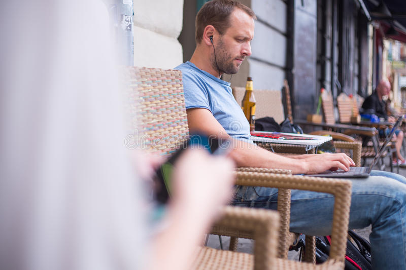 Man With Headphones Sitting Outdoors Using A Laptop Computer. Stock Photo