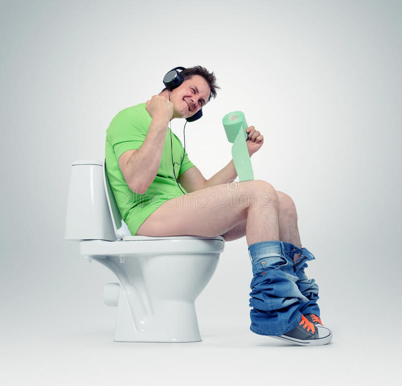 Man in headphones sitting on the toilet. Yes!. Situation concept stock photo